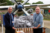 Richard Stanton presented a large photograph of 'Whiskey Fox' on the production line at Weybridge, Surrey, England to John Overhill.